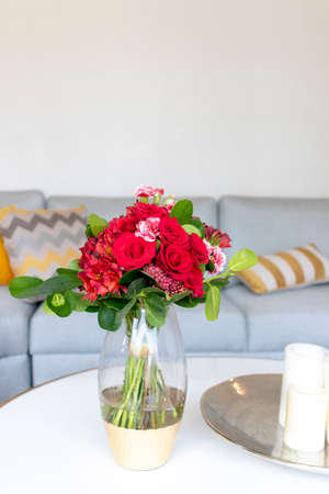 Arrangement of roses and red carnations