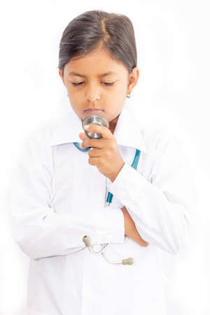 Cute little girl doctor, with stethoscope and white medical uniform Imagens