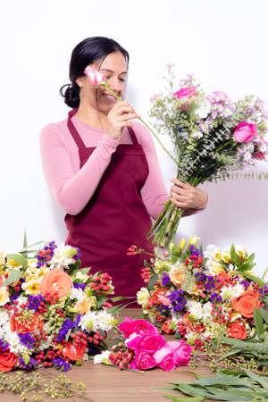 Brunette woman making bouquets at the florist shop Imagens