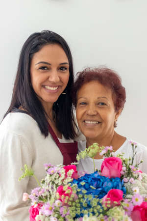 Smiling mother and daughter with their bouquet of flowers