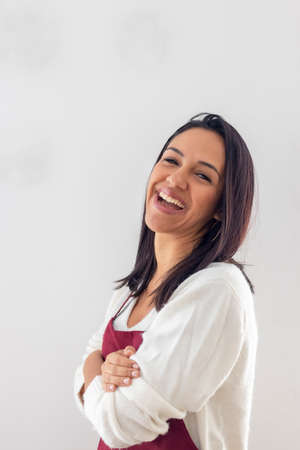 Cute smiling brunette with her apron placed Imagens