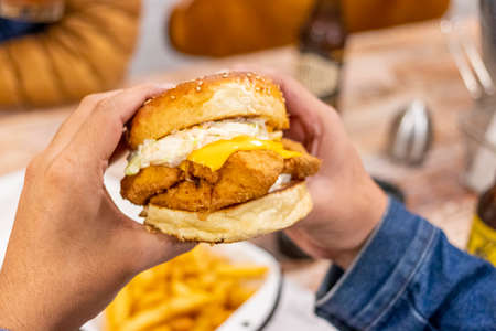 Young man eating a chicken burger with cheddar cheese