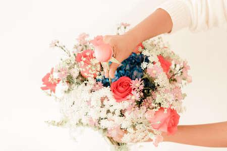 Womans hand decorating floral arrangement
