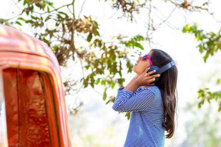 Little girl listening to music with her headphones in the truck car Foto de archivo - 138300460