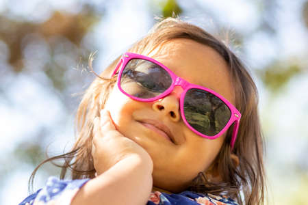 Cute little girl with pink sunglasses and hands on her face. Foto de archivo - 138300015