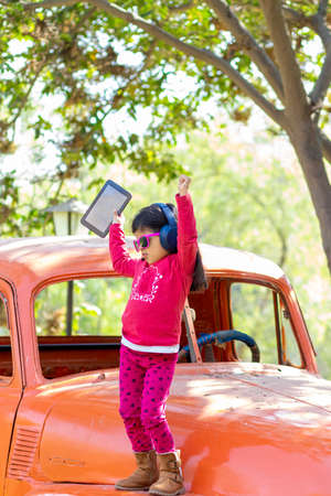Little girl listening to music on the tablet with her headphones in the truck car Foto de archivo - 138300494