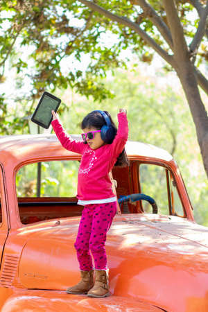 Little girl listening to music on the tablet with her headphones in the truck car Foto de archivo - 138299994