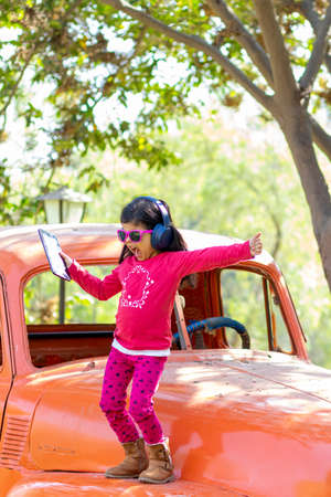 Little girl listening to music on the tablet with her headphones in the truck car Foto de archivo - 138299685