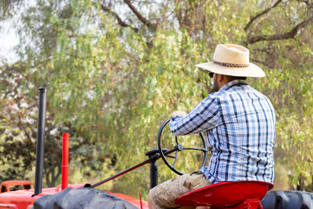 Handsome man with sunglasses driving the tractor to work on the farm Stockfoto