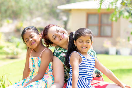 Love between a young mother and her two pretty daughters outdoors