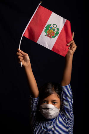 Portrait of little Peruvian girl wearing medical mask and holding hopefully the flag of Peru
