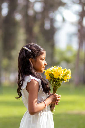 Little girl in white dress and with a cute bouquet of flowers in her hand
