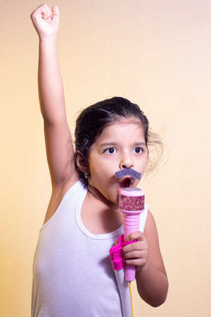 Little girl with a mustache singing using her microphone
