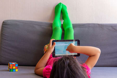 Little girl playing with her tablet lying on the sofa