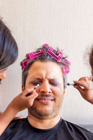 Handsome father is being makeup by the hands of his daughters