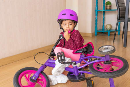 Sad little girl fell to the ground while playing with her bicycle in the house