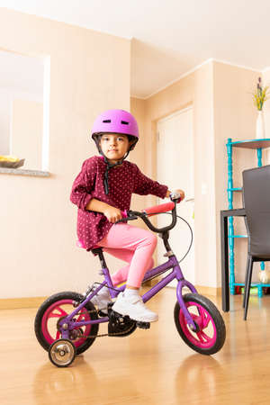 Little girl is riding a bicycle in her living room