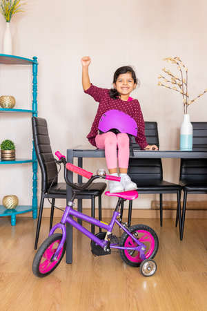 Little girl playing her bicycle in the living room of the apartment during quarantine