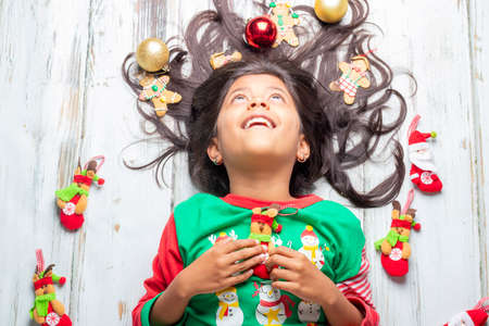 Cute cheerful smiling girl with decorated Christmas hair