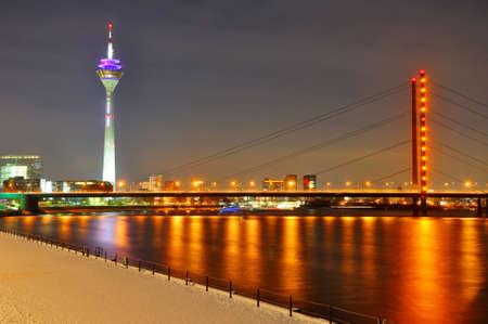 rhein: Beautiful night shore of Rhein river at night in Dusseldorf with a Rheinturm tower and a bridge, Nordrhein-Westfalen, Germany Stock Photo