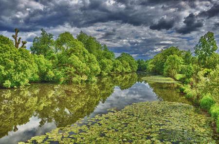 unruffled: Fulda river in HDR Aueweiher Park  in Fulda, Hessen, Germany Stock Photo