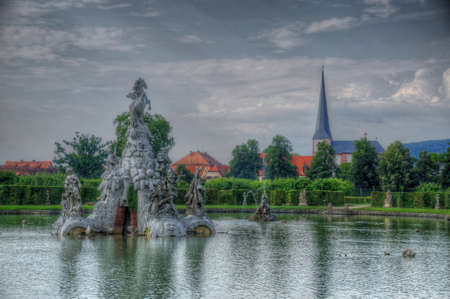 riverside landscaping: Lake with fontains in Rokokogarten (Garden Rokoko), Wurzburg, Bayern, Germany Stock Photo
