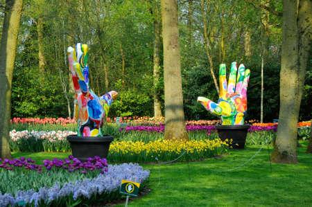 Groene Vingers (Grote kleurrijke handen) met tulpen in de Keukenhof park in Nederland