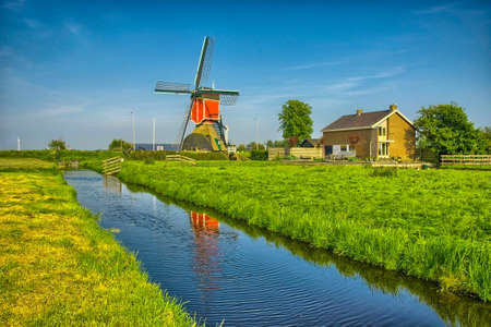 holland windmill: Windmills and water canal in Kinderdijk, Holland or Netherlands.  Stock Photo