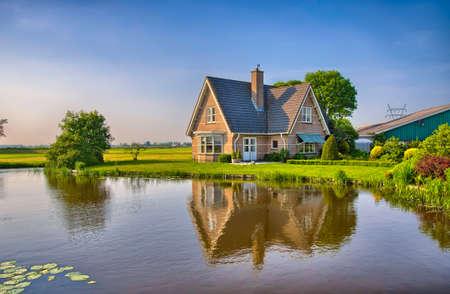 krajina: Červené cihly dům v přírodě nedaleko jezera se zrcadlovým odrazem ve vodě, Amsterdam, Holandsko, Nizozemsko, HDR
