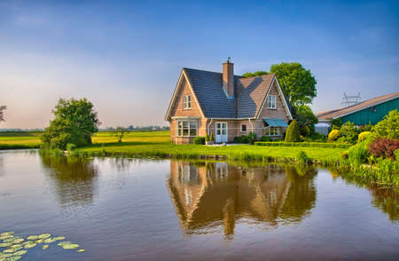 holland: Red bricks house in countryside near the lake with mirror reflection in water, Amsterdam, Holland, Netherlands, HDR