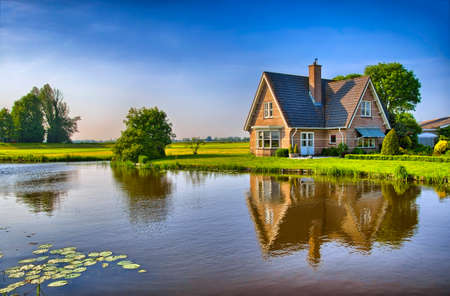 Red bricks house in countryside near the lake with mirror reflection in water, Amsterdam, Holland, Netherlands, HDR