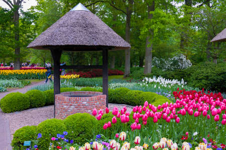 water garden: Well with colorful tulips in Keukenhof Park, Lisse in Holland. Stock Photo