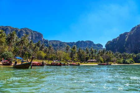 Long tail boats on tropical beach with palms, Tonsai Bay, Railay Beach, Ao Nang, Krabi, Thailand Stock Photo