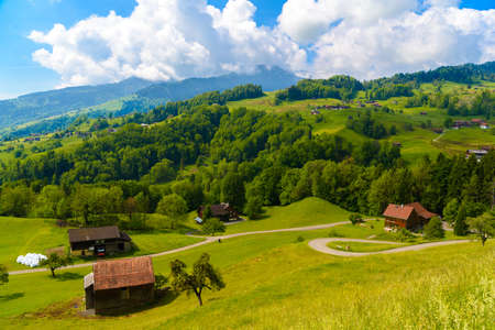 Wooden cottage houses on green fields, Grabs, Werdenberg, St. Gallen Switzerland Archivio Fotografico