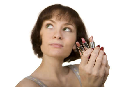 a photo of a young woman choosing a lipstick photo