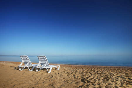 a photo of empty beach with two sunchairs photo