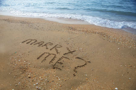marriage proposal: a photo of marriage proposal written on sandy beach Stock Photo