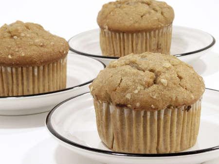 Oat breakfast muffins on saucers against white background. Standard-Bild