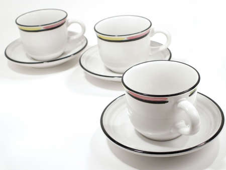 Beverage cups with colorful rims, and saucers receede to upper left on white background. Standard-Bild