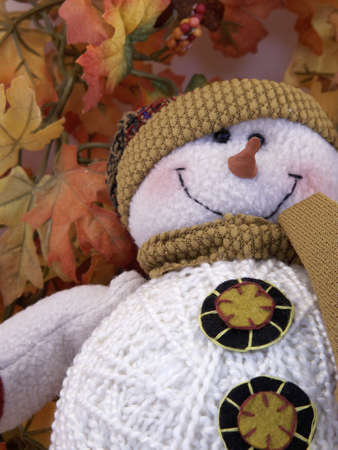 Close-up of snowman dressed for fall on bed of leaves.