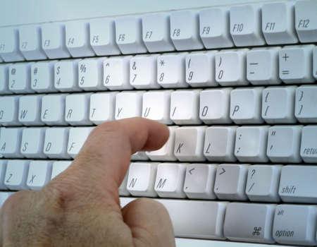 One finger punches key on white keyboard. Standard-Bild