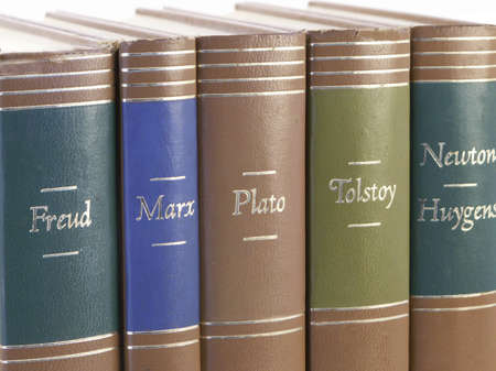 Leather bound books by great historic authors stand together with isolated white background.