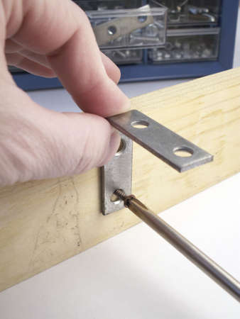 Fingers and thumb hold L-bracket in place as screw is driven in to board to secure it.