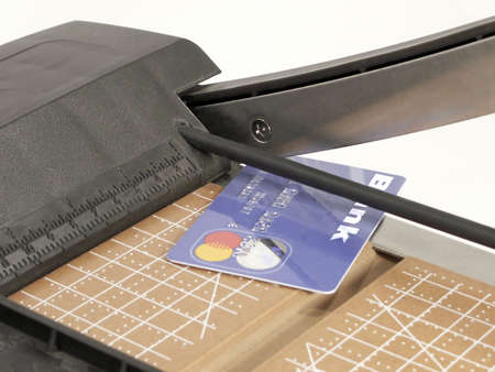 Credit card on cutting board with cutting blade raised.