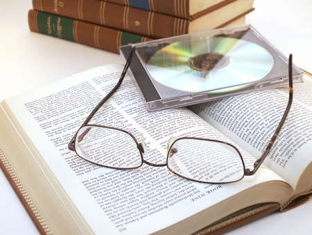 Glasses and CD in case lie on open book with more leather bound books in background. Reklamní fotografie - 270626