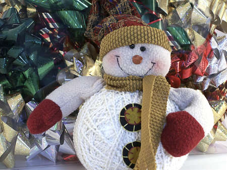 Smiling snowman in stocking hat sits in front of stack of colorful bows.