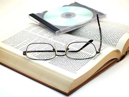 Pair of glasses rest on open book with CD on top. Standard-Bild