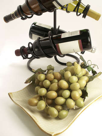 Grapes sit on serving plate in foreground with bottles of wine in metal holder behind. Standard-Bild