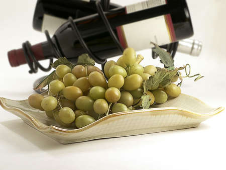 Green grapes sit on serving dish with wine bottles in rack behind.