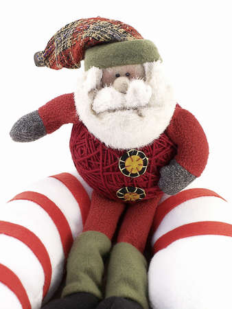 Crafted Santa sits on giant candy-cane, with white background.